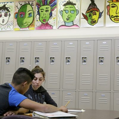 In this April 19, 2016, photo, Laurie Millan, a para-professional and tutor, works with a student during an after-school tutoring session at San Francisco International High School, in San Francisco. While some districts in numerous states have discouraged migrant minors from Central America from enrolling in their schools, San Francisco International High School accommodated its youths by rewriting young-adult novels at a basic level to spark the newcomers' interest in reading. (AP Photo/Jeff Chiu)