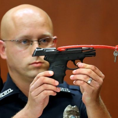 FILE- In this June 28, 2013, file photo, Sanford police officer Timothy Smith holds up the gun that was used to kill Trayvon Martin, while testifying in the George Zimmerman trial, in Seminole circuit court in Sanford, Fla. The pistol former neighborhood watch volunteer Zimmerman used in the fatal shooting of Martin is going up for auction online. (AP Photo/Orlando Sentinel, Joe Burbank, Pool, File)