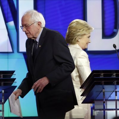 Democratic presidential candidates Sen. Bernie Sanders, I-Vt, left, and Hillary Clinton pass at the start of a break during the CNN Democratic Presidential Primary Debate at the Brooklyn Navy Yard on Thursday, April 14, 2016 in New York. (AP Photo/Seth Wenig)