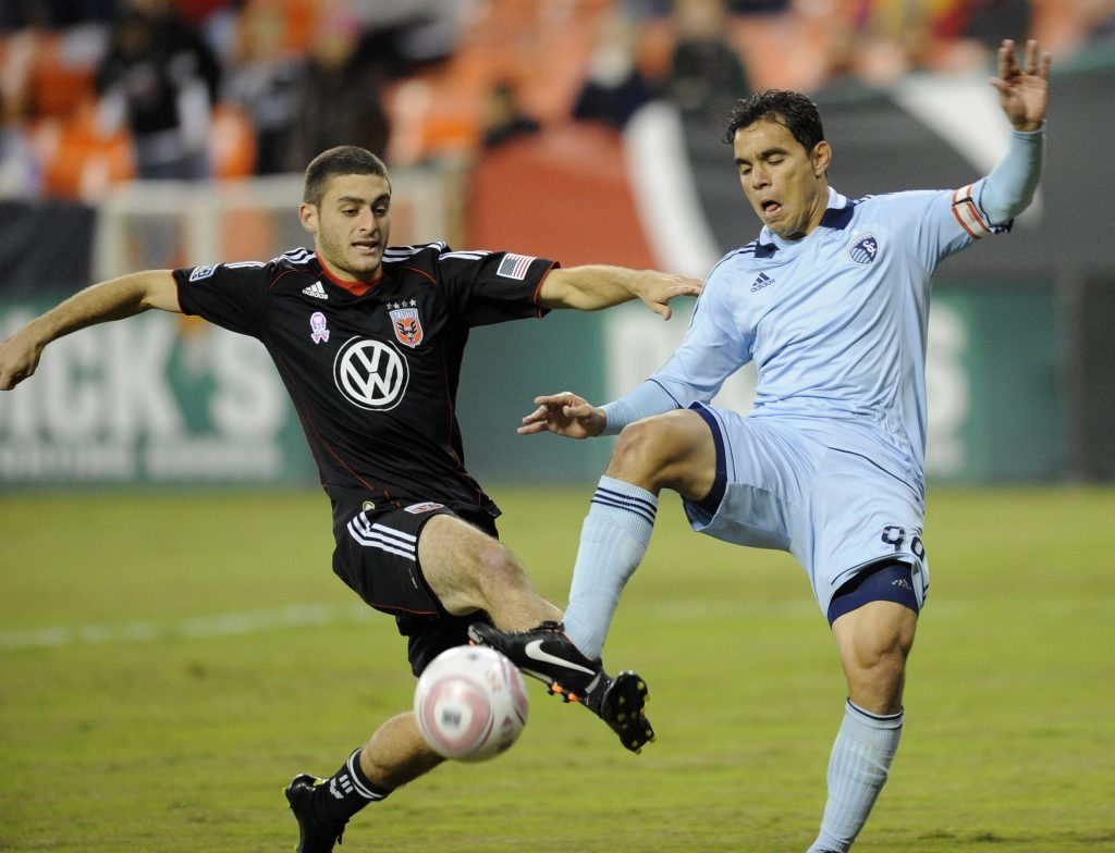 D.C. United defender Chris Korb, left, battles for the ball against Sporting Kansas City's Omar Bravo, right, during the first half of an MLS soccer game, Saturday, Oct. 22, in Washington. (AP Photo/Nick Wass)