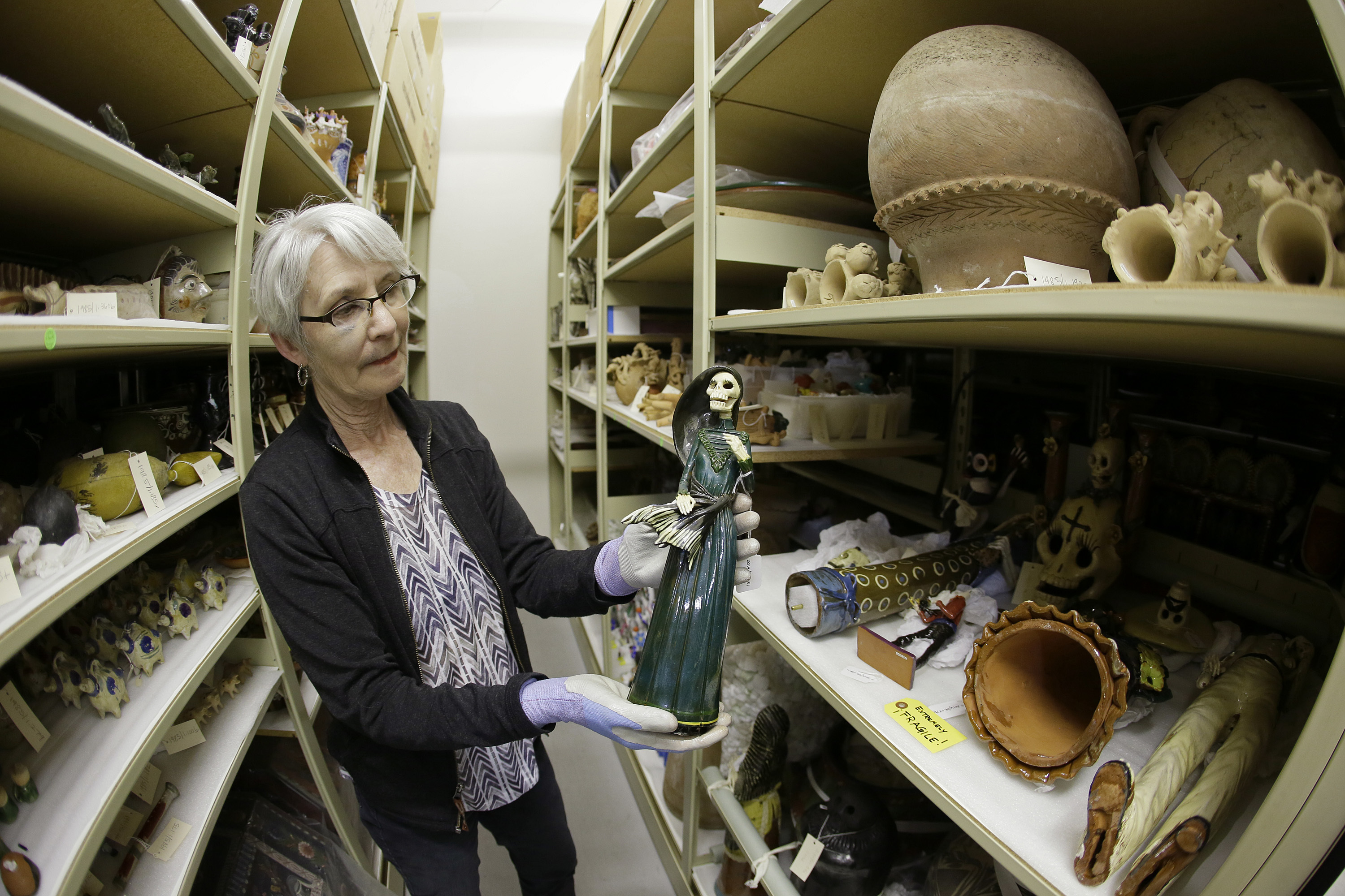 "In this photo taken Monday, June 27, 2016, registrar Wendy Niles holds a Day of the Dead sculpture ""La Soldadera"" by Alvaro de la Cruz being stored in a vault at the Mexican Museum currently located at Fort Mason in San Francisco. Construction of a four-story, state-of-the-art Mexican Museum is underway, realizing the dream of a late Mexican-American artist who four decades ago opened the city's first museum for Latino art in a Mission District storefront. The 60-000 square feet building in downtown San Francisco will be home to 16,000 pre-Columbian, colonial, modern and contemporary works of Mexican, Mexican-American and Latino art, the largest such collection in the country. (AP Photo/Eric Risberg)"