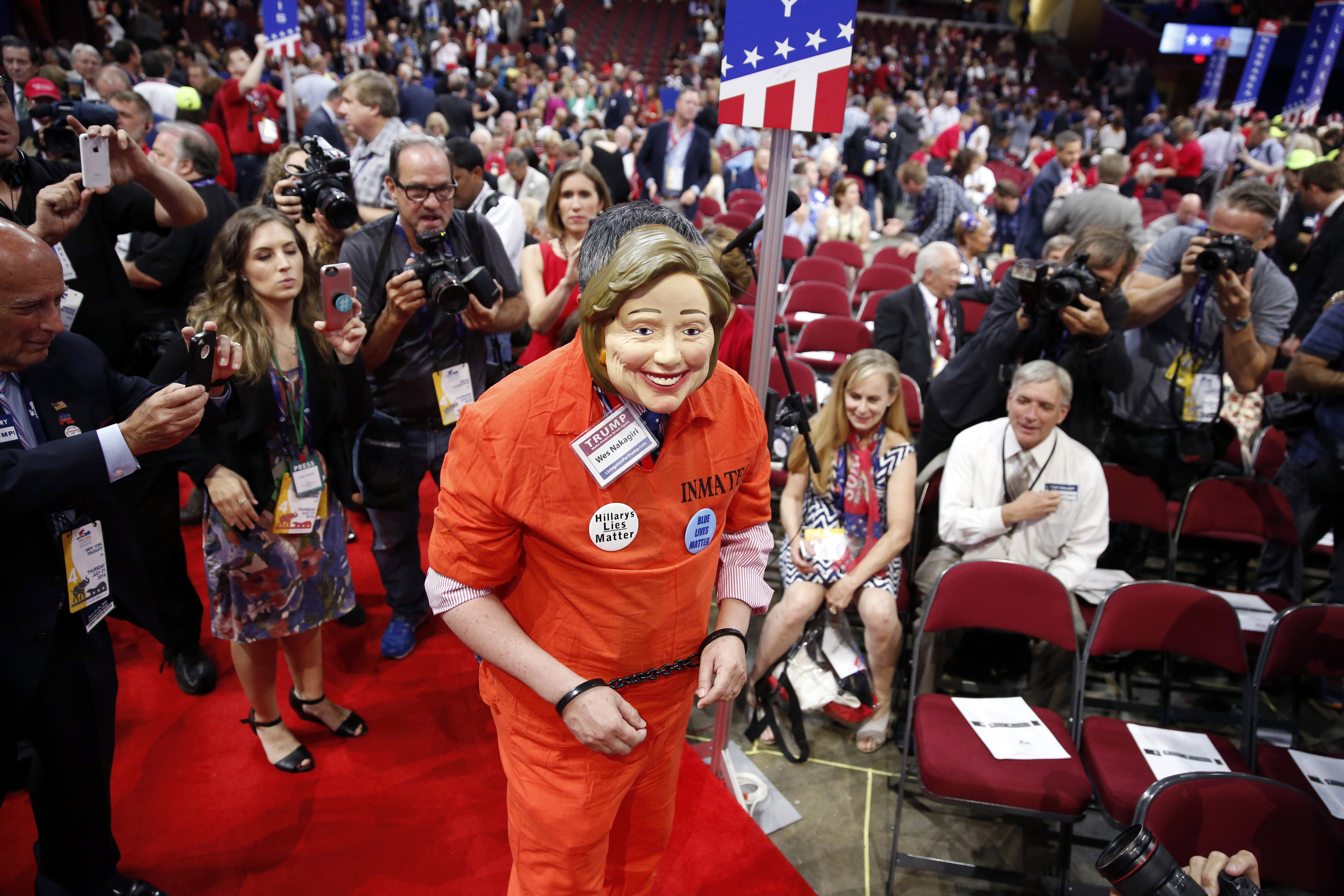 Michigan delegate Wes Nakagiri walks around in a jumpsuit with a Hillary Clinton mask before the final day of the Republican National Convention in Cleveland, Thursday, July 21, 2016. (AP Photo/Matt Rourke)