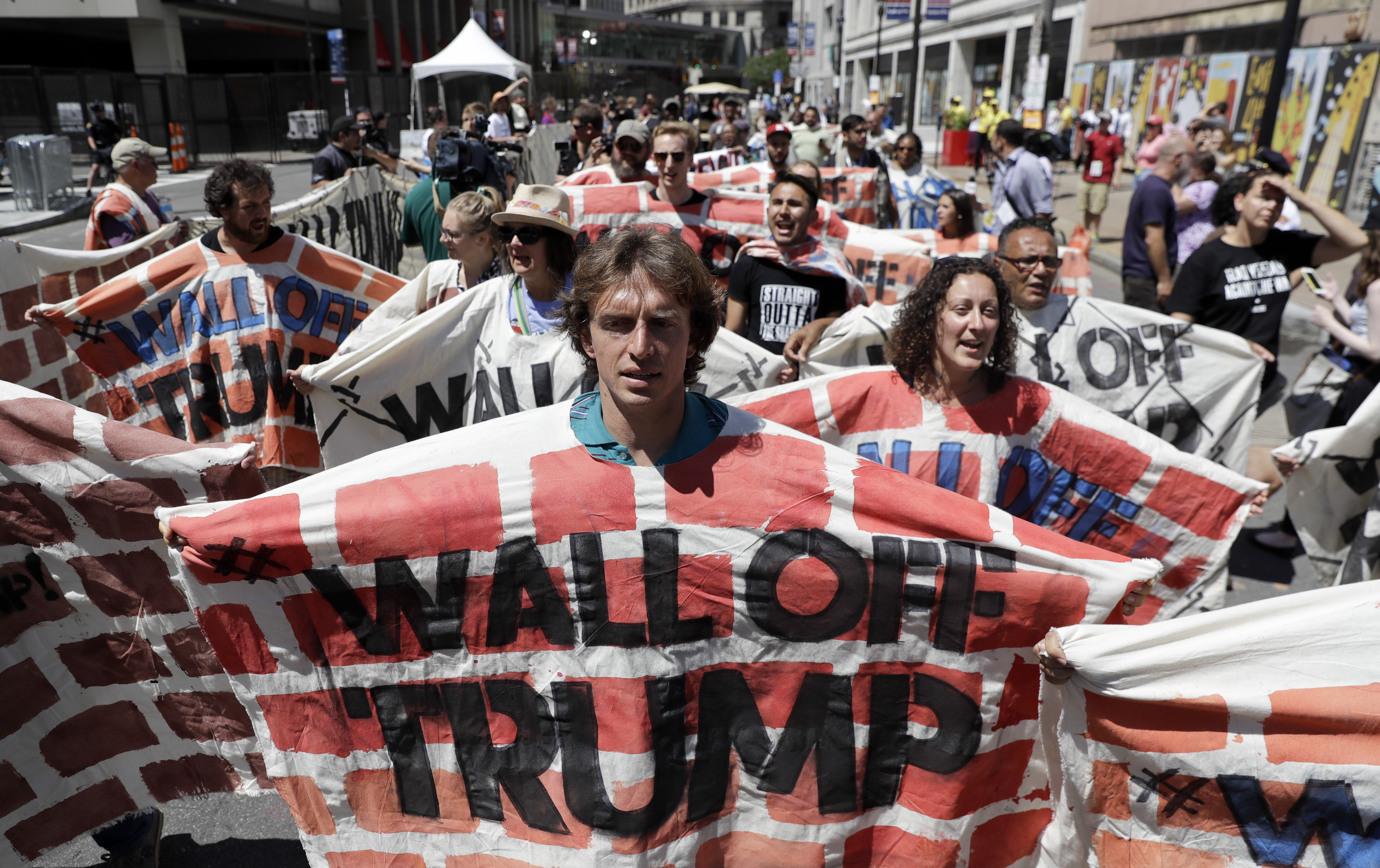 Immigrant rights activists hold up a fabric wall protesting Republican presidential candidate Donald Trump, Wednesday, July 20, 2016, in Cleveland, during the third day of the Republican convention. (AP Photo/Patrick Semansky)
