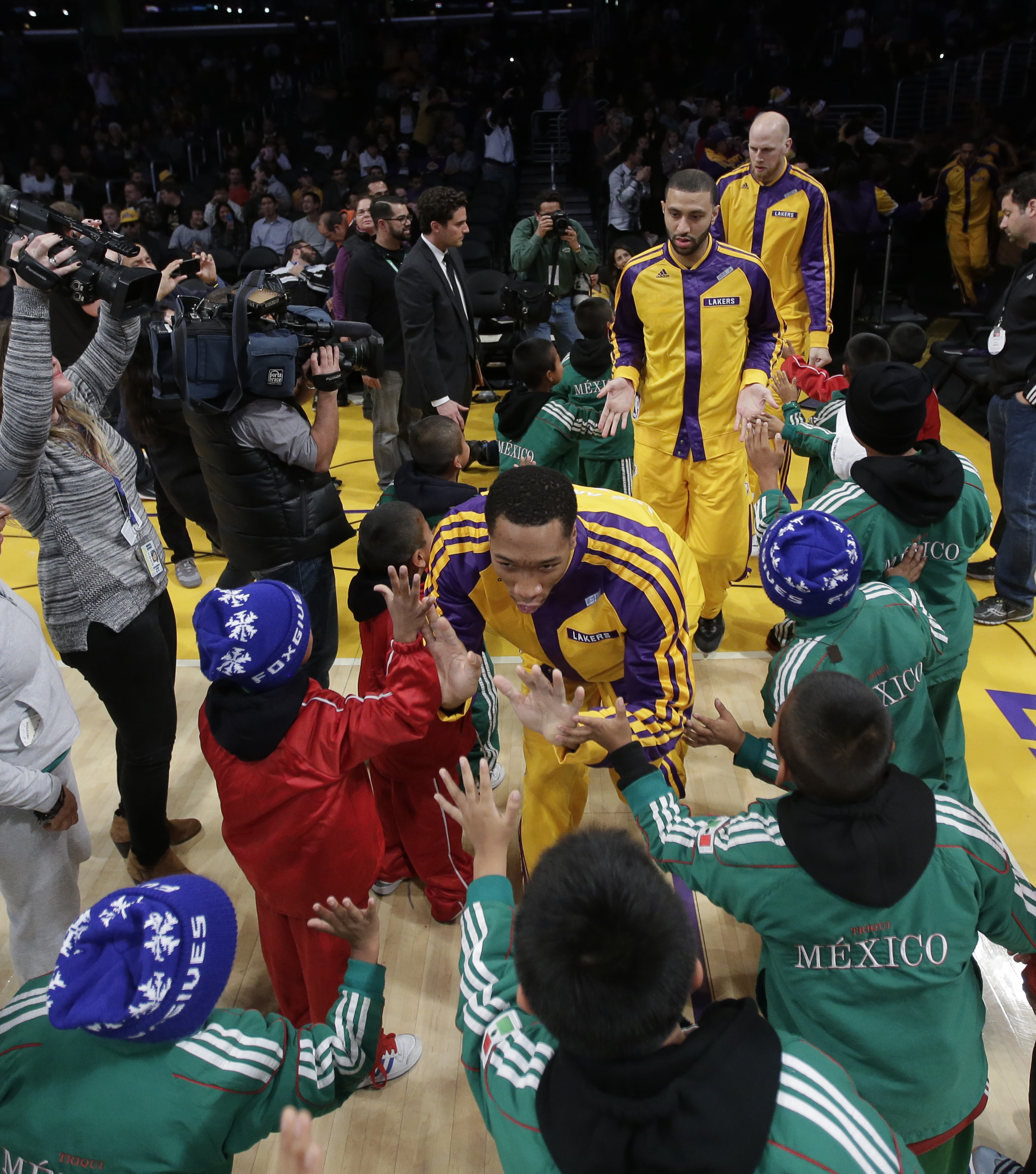 Members of Triqui kids basketball team, made up of children from the mountainous region of Oaxaca, Mexico, greet the Los Angeles Lakers before an NBA basketball game against the Minnesota Timberwolves in Los Angeles, Friday, Dec. 20, 2013. (AP Photo/Chris Carlson)