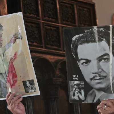 A man holds up laminated posters depicting the late Mexican Mario Moreno known as