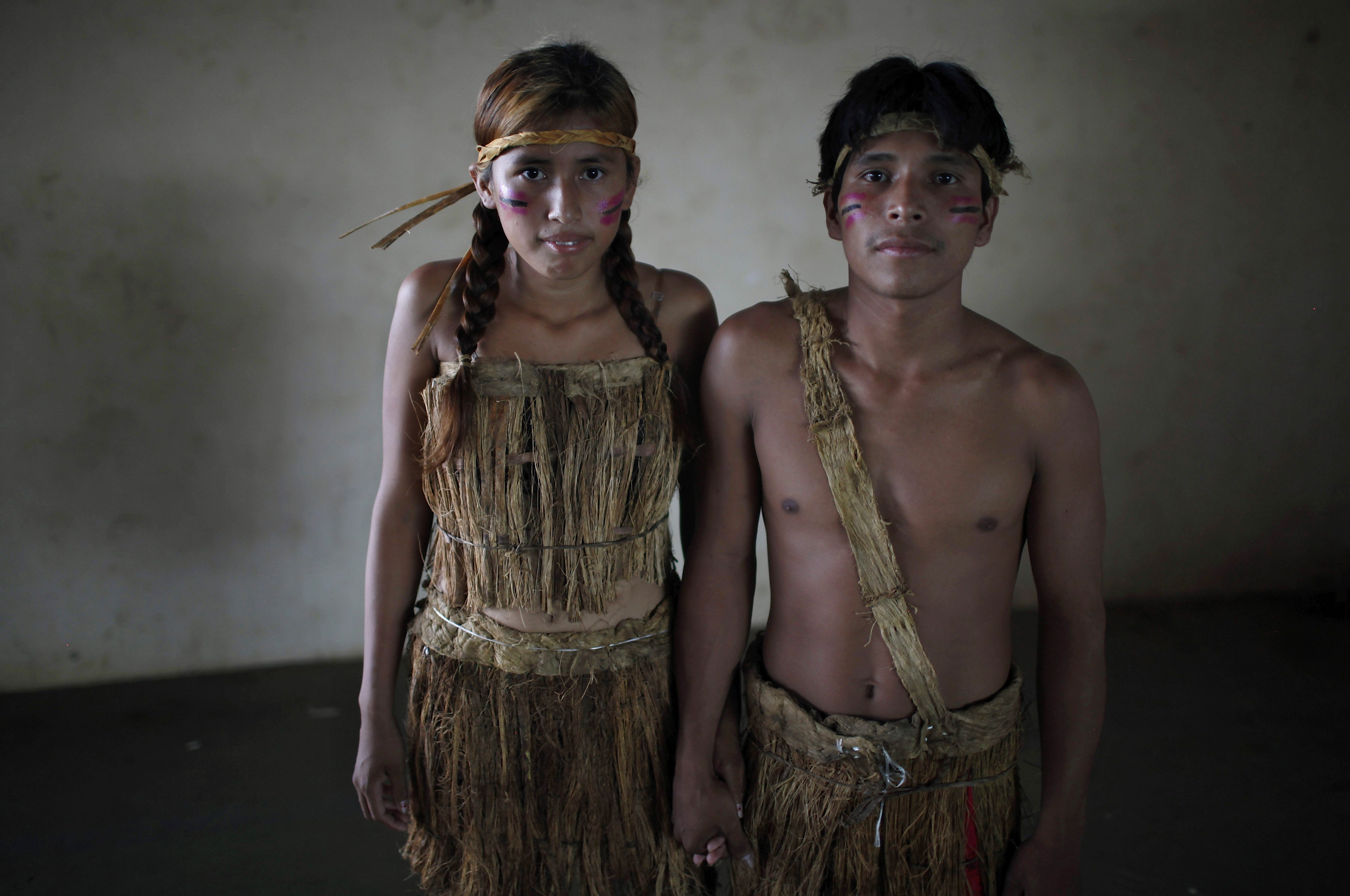 """Erika Kanacmi, left, and Denis Capi, an Esse Ejja indigenous couple, pose for a portrait before a collective wedding ceremony in Cobija, Bolivia, Saturday, Oct. 6, 2012. Indigenous couples from Bolivia's Amazon region got married in a mass wedding coined """"Collective Marriage from our Identity 2012,"""" organized by the government. Many of the couples were already legally married, but wanted to attend a ceremony that included some indigenous traditions from the Amazon. (AP Photo/Juan Karita)"""
