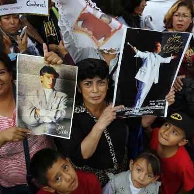 Admiradores sostienen afiches del cantante y compositor mexicano Juan Gabriel mientras esperan para rendirle sus últimos honores afuera del Palacio de Bellas Artes, en la Ciudad de México, el lunes 5 de septiembre del 2016. (AP Foto/Marco Ugarte)