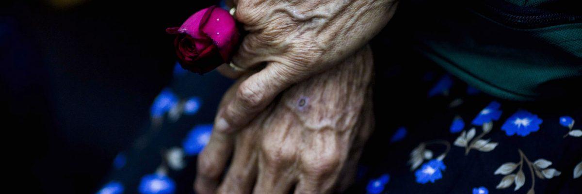 En imagen de archivo del 2 de agosto de 2011, Cristina Alfaro Mejía, cuyos esposo e hija fueron asesinados por un comando del ejército durante una matanza en la comunidad de Las Dos Erres en 1982, sostiene una rosa mientras espera la sentencia de soldados en la ciudad de Guatemala. La masacre, en que según las investigaciones de la fiscalía más de 200 personas fueron asesinadas, es llevada al cine en un documental bajo la producción del cineasta Steven Spielberg. (AP Foto/Rodrigo Abd, archivo)