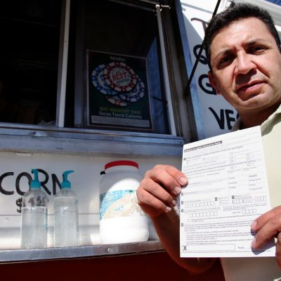 Carlos Zamora shows a voter registration card from a pile placed on the counter of the Tierra Caliente taco truck on Thursday, Sept. 29, 2016, in Houston. Zamora is with Mi Familia Vota, a Latino activist group that seeks to register more voters in the Latino community. Mi Familia Vota partnered with a local design firm to make eight of the city's taco trucks into mobile voter registration booths after a surrogate of Republican presidential candidate Donald Trump recently suggested that unless the United States fortifies its borders and tightens immigration limits,