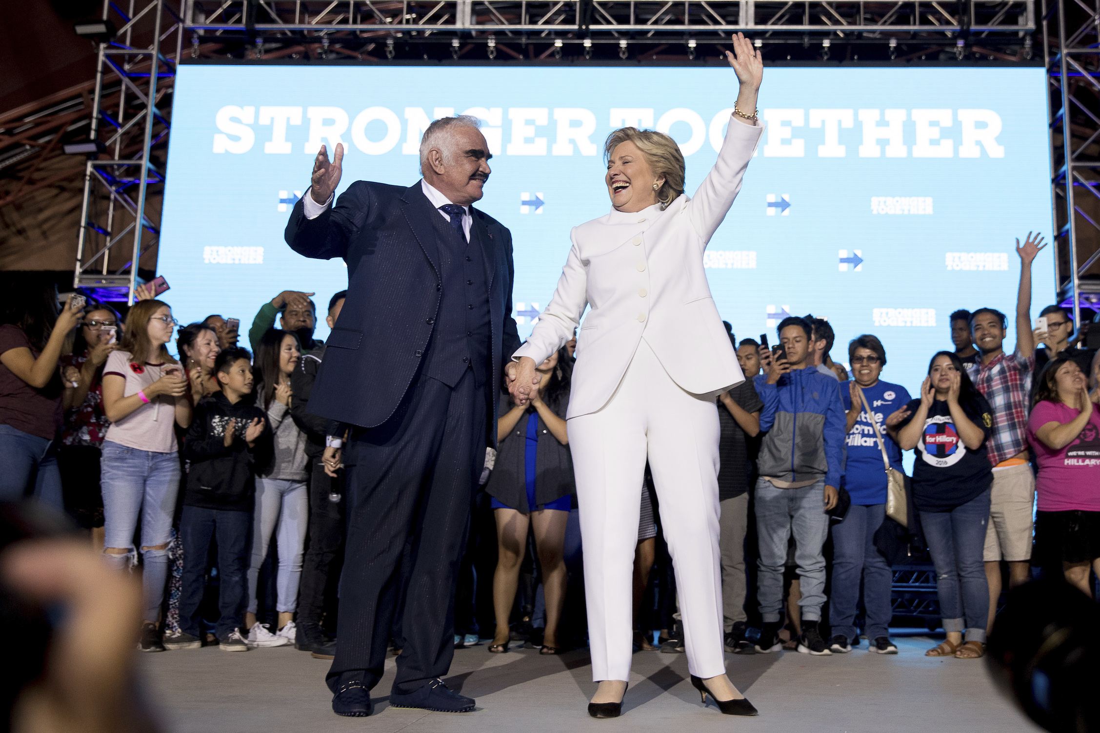 Democratic presidential candidate Hillary Clinton, right, and singer Vicente Fernandez, left, stand on stage together at debate watch party at the Craig Ranch Regional Amphitheater in North Las Vegas, Wednesday, Oct. 19, 2016, following the third presidential debate. (AP Photo/Andrew Harnik)