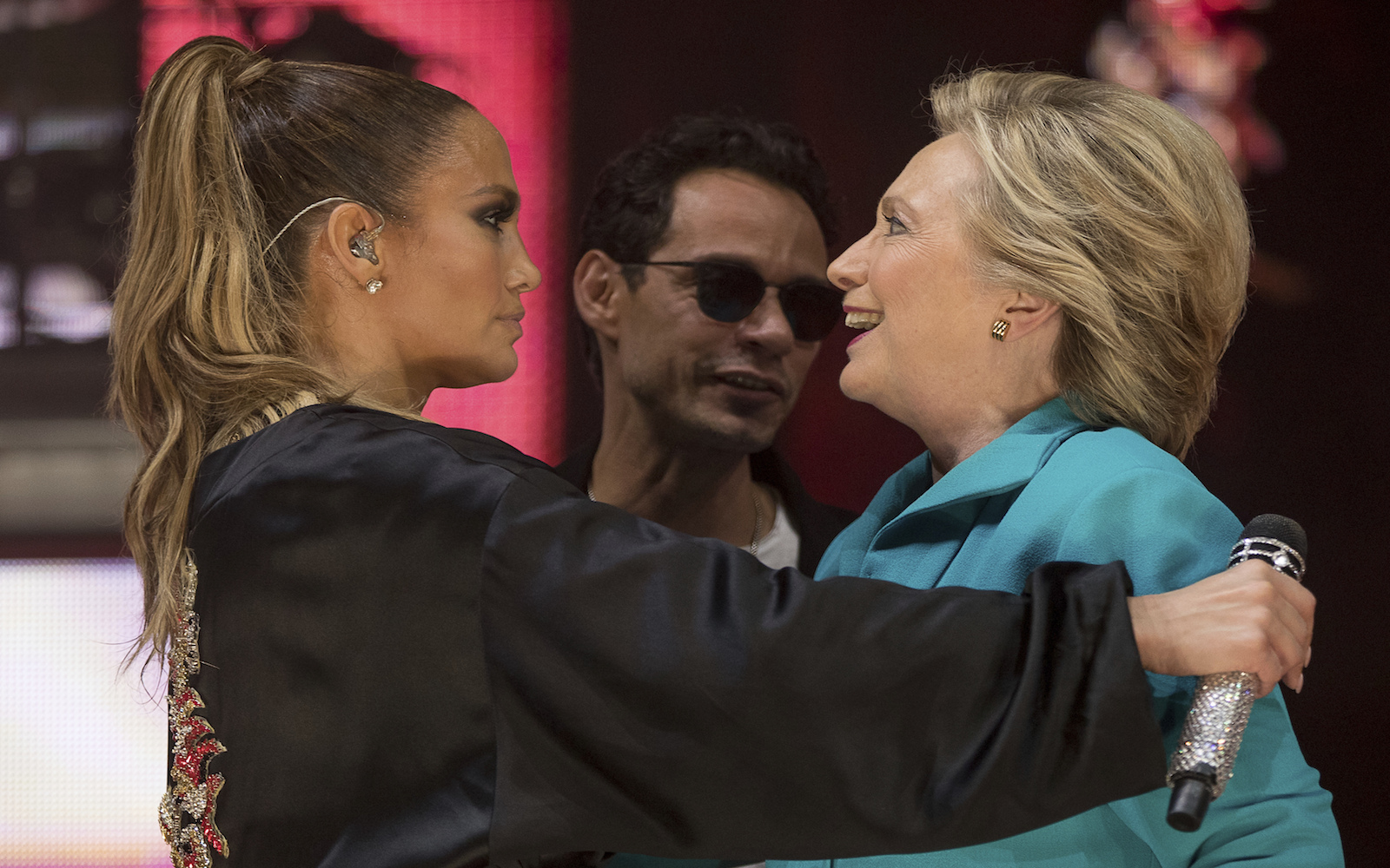 Democratic presidential candidate Hillary Clinton, right, accompanied by singer-songwriter Marc Anthony, center, hugs performer Jennifer Lopez, left, at a Get Out The Vote performance at Bayfront Park Amphitheater in Miami, Saturday, Oct. 29, 2016. (AP Photo/Andrew Harnik)