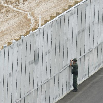 Un agente de la Patrulla Fronteriza echa un vistazo a través de una cerca limítrofe en San Diego en una sección que es parte de la zona