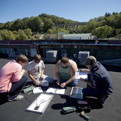 FILE - In this Oct. 5, 2015 file photo, people learn solar panel installation on the roof of the Coalfield Development Corporation during a class in Huntington, W.Va. Mostly unnoticed amid the political brawl over climate change, America has undergone a quiet transformation in how and where it gets its energy during Barack Obama's presidency, slicing the nation's output of polluting gases that are warming Earth.  (AP Photo/David Goldman, File)